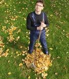 从事园艺,倾斜在秋天的叶子 免版税库存照片