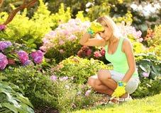 从事园艺 种植花的白肤金发的妇女在庭院里 免版税库存图片