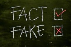 事实或伪造品写与颜色白垩概念在黑板 免版税图库摄影