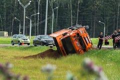 事故车祸机动车路路 卡车用沙子装载了被翻转入路旁 库存照片