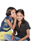 二个印第安孩子说闲话彼此。 库存照片