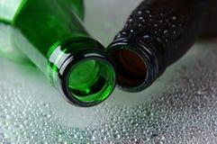二个啤酒瓶特写镜头在湿表面的 免版税库存图片