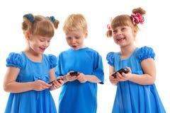 二个女孩和有他们的移动电话的一个男孩 免版税库存照片