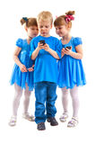 二个女孩和有他们的移动电话的一个男孩 图库摄影