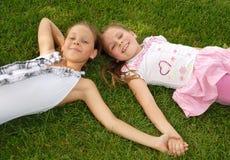 二个女孩在绿草位于 库存照片