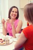 女孩坐厨房和谈 免版税库存图片