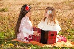 二个女孩姐妹在草读了书 免版税库存图片