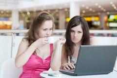 二个女孩研究膝上型计算机 库存图片