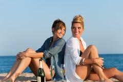 二个女孩紧接坐海滩。 库存图片