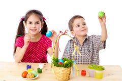 二个孩子油漆复活节彩蛋 图库摄影