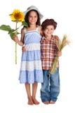 二个孩子用向日葵和麦子 库存图片
