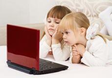 二个小女孩是与膝上型计算机 免版税库存图片