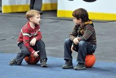 二个小男孩坐球 免版税库存图片