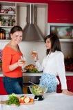 二个少妇在现代厨房里 免版税库存图片