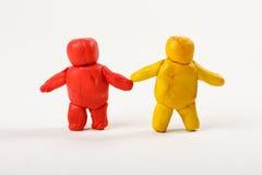 二个彩色塑泥人。 突出在空白bac 免版税库存图片