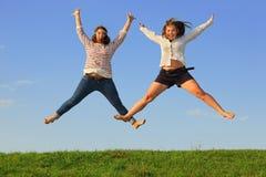 二个新肥胖女孩跳在草 库存照片