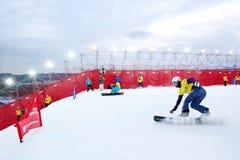 二个未认出的人乘坐雪板 库存照片