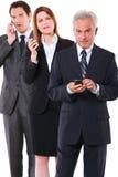 二个生意人和有移动电话的一名女实业家 免版税图库摄影