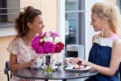 二个美丽的女孩在夏天装备坐在表 库存照片