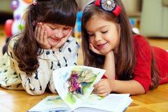 二个美丽的女孩阅读书在家 免版税库存图片