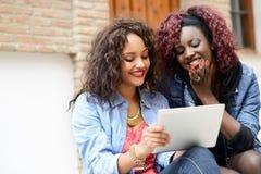 有片剂计算机的二个美丽的女孩在都市backgrund 库存图片