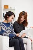 二使用片剂个人计算机的亚裔少妇。 免版税库存照片
