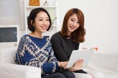 二使用片剂个人计算机的亚裔少妇。 库存图片