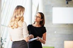二名女实业家开非正式会议在现代办公室 免版税库存照片