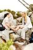 二名妇女互相帮助,在他们中的一个秋天之后 库存图片