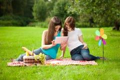 二名妇女在一顿野餐的公园与片剂个人计算机 免版税库存图片