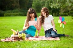 二名妇女在一顿野餐的公园与片剂个人计算机 免版税图库摄影