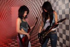 二名妇女在工作室弹电吉他 免版税库存图片
