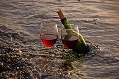 二块玻璃红葡萄酒和瓶在海洋 免版税库存照片