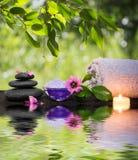 二块蜡烛和毛巾染黑石头和在水的紫色花 库存图片