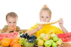 二子项吃果子在表 图库摄影
