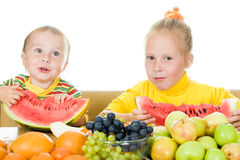 二子项吃果子在表 免版税库存照片