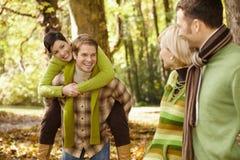 二对夫妇获得乐趣在秋天公园 免版税库存照片