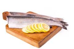 二条分开的鳟鱼用准备好的柠檬被烹调 免版税库存照片