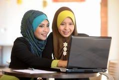 使用膝上型计算机的二条围巾女孩 免版税图库摄影