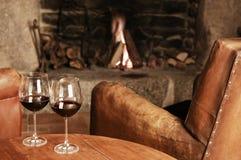 二杯在一个舒适壁炉的红葡萄酒 库存照片