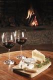 二杯在一个舒适壁炉的红葡萄酒 免版税库存图片