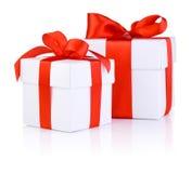 二白色箱子附加与一条红色缎丝带鞠躬 免版税库存照片