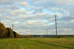 二面对切的领域在秋天,输电线支持,黄绿色森林, Kostroma地区,俄罗斯 免版税库存照片