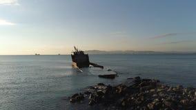 于蓝色,多云天空和发光的太阳背景的蓝色海沉没的生锈的被击毁的船 射击 在海岸附近的救生艇 股票视频