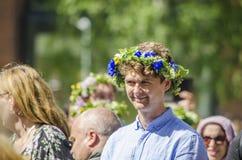 于默奥,瑞典-蓝色衬衣的2019 6月21日,人享用瑞典传统中间summerday的在与五颜六色的花的一好日子 库存照片
