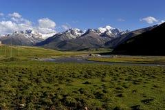 云彩、积雪覆盖的山和河和草甸 库存图片