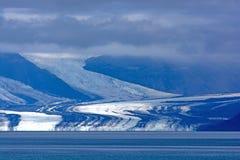 从云彩出来的冰川 免版税库存照片