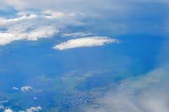 云彩和地球的看法从舷窗,从高度10,000米 免版税库存图片