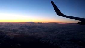 云彩和天空作为一个航空器的进行下去的窗口-在晚上在城市上 影视素材