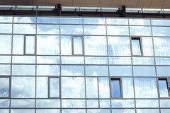 云彩和天空反射在一个现代城市大厦的窗口- 库存照片